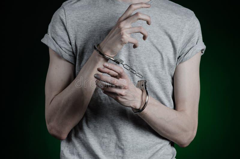 Więźniarski i skazujący temat: mężczyzna z kajdankami na jego rękach w szarej koszulce i niebieskich dżinsach na ciemnozielonym t zdjęcia stock