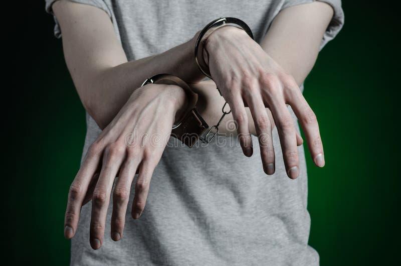 Więźniarski i skazujący temat: mężczyzna z kajdankami na jego rękach w szarej koszulce i niebieskich dżinsach na ciemnozielonym t obrazy stock