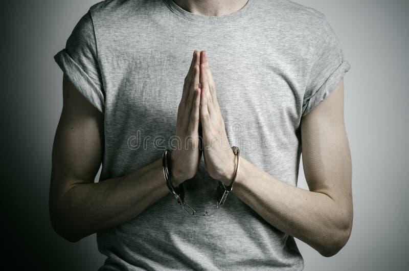 Więźniarski i skazujący temat: mężczyzna z kajdankami na jego rękach w szarej koszulce na szarym tle w studiu, stawia kajdanki da zdjęcia stock