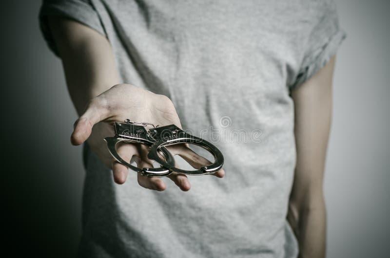 Więźniarski i skazujący temat: mężczyzna z kajdankami na jego rękach w szarej koszulce na szarym tle w studiu, stawia kajdanki da obrazy royalty free