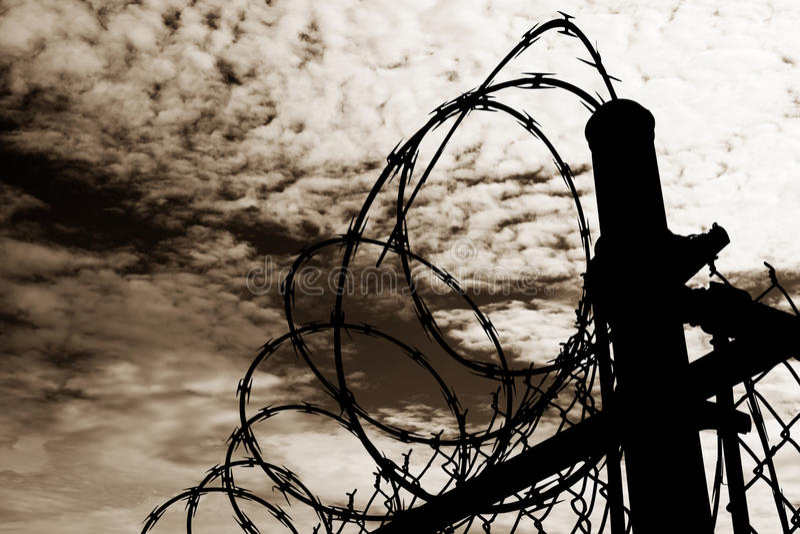 Więzienia ogrodzenie Przeciw Ciemnemu niebu fotografia stock
