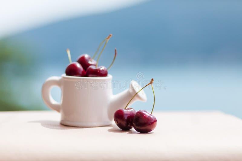 Wiśnie w białej wazie na balkonie z widokiem morze i góry Czerwona dojrzała świeża wiśnia na stole w lecie fotografia royalty free