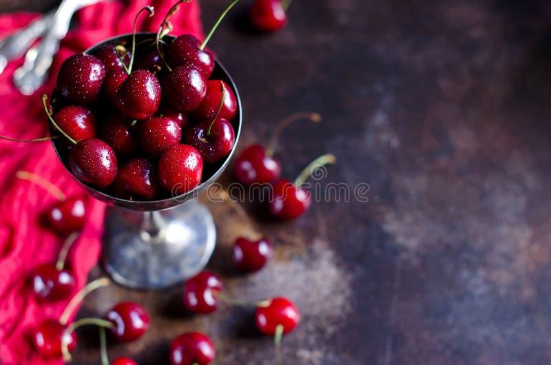 Wiśnie z kroplami rosa zamykają w górę wazy wewnątrz zdjęcie royalty free