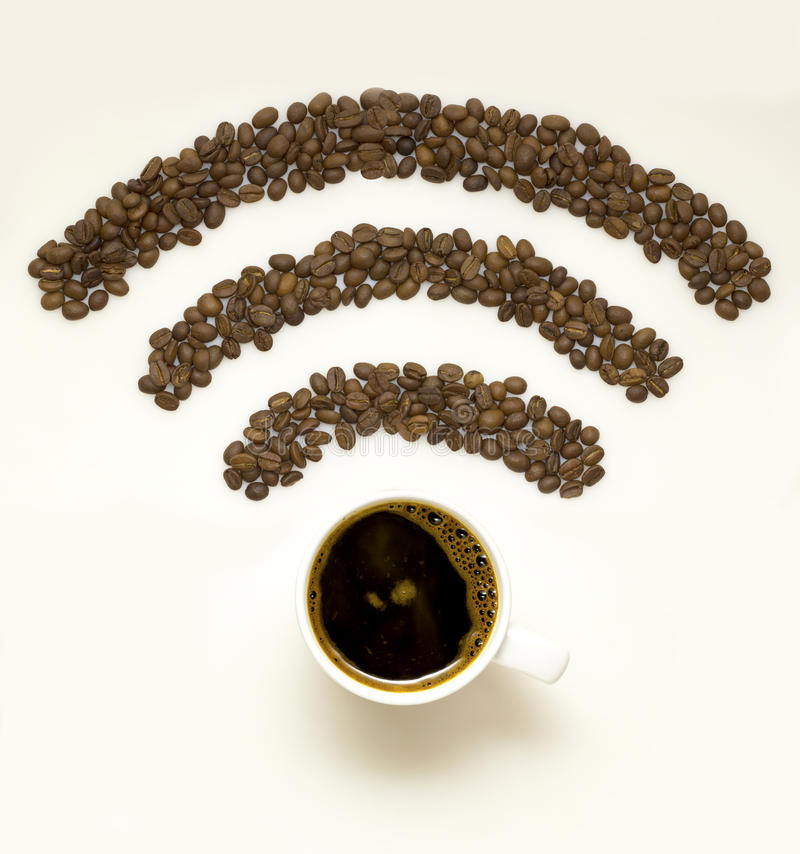Wi-fi coffee. Creative concept photo of a cup with coffee beans in the shape of wi-fi sign on white background stock image