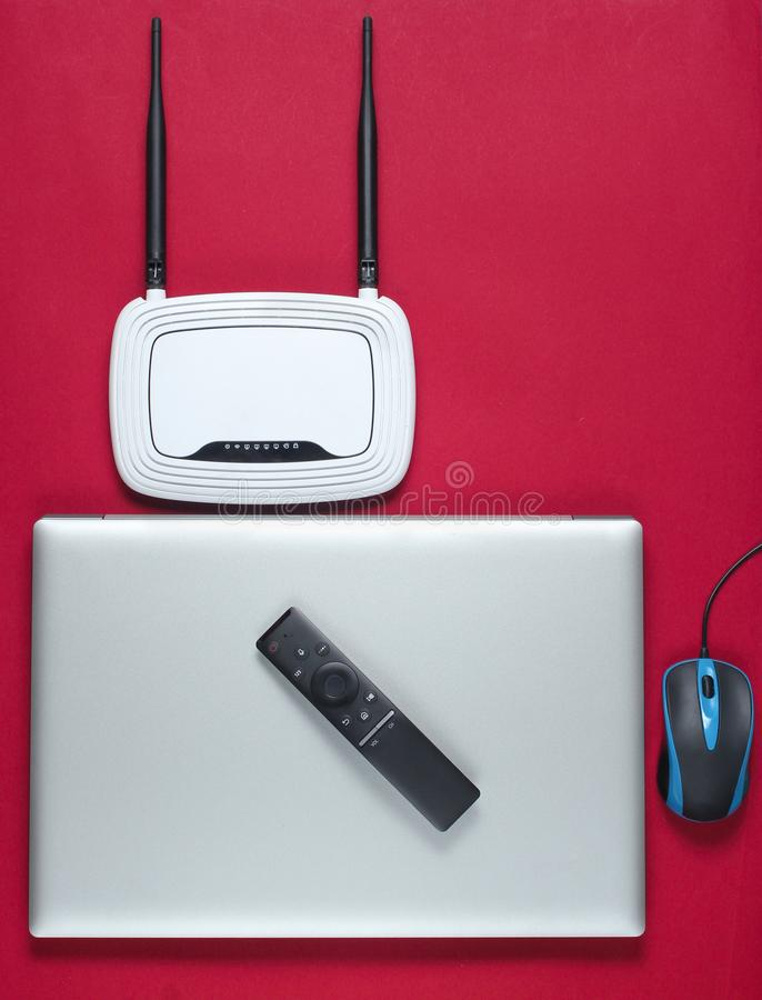 Wi fi router, laptop, pc mouse, remote controller. On red background. Top view stock photography