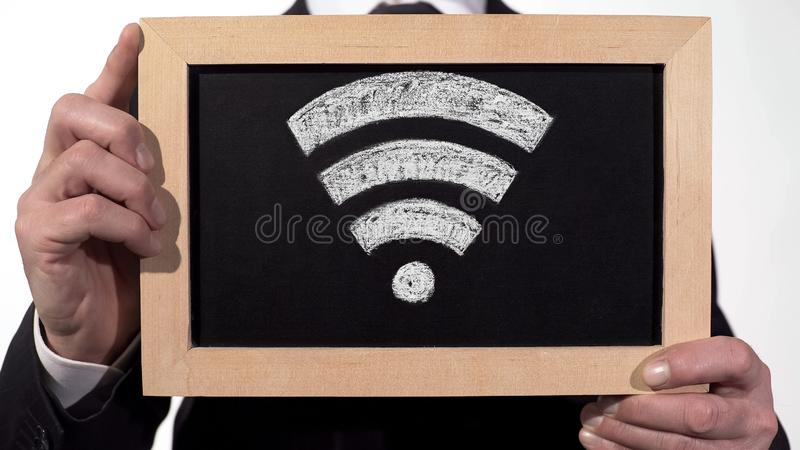 Wi-Fi zone sign drawn on blackboard in businessman hands, internet technology royalty free stock image