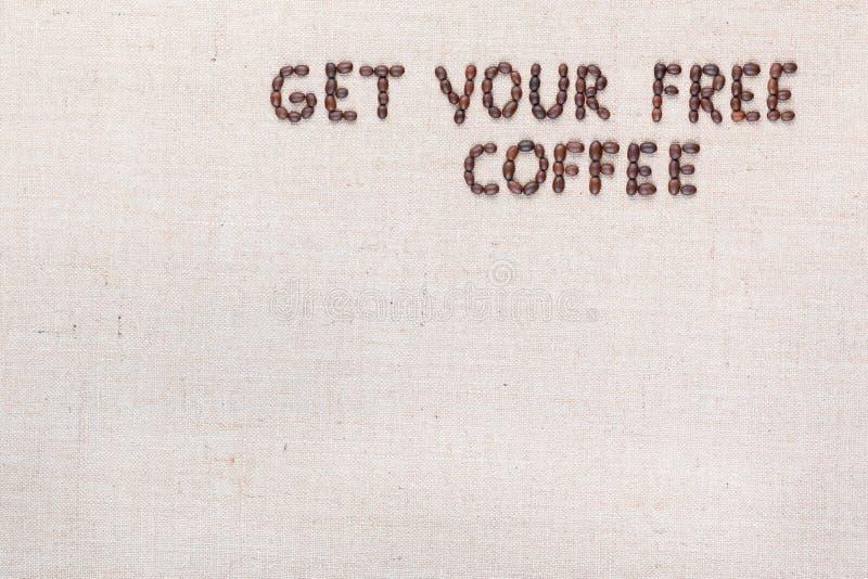 Wiadomo?? Dostaje tw?j bezp?atn? kaw? pisze z kawowymi fasolami, wyr?wnywa? przy odg?rnym dobrem zdjęcia royalty free