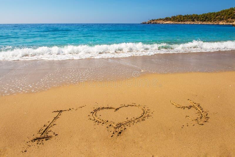 Wiadomość kocham ciebie na piasek plaży zdjęcie stock