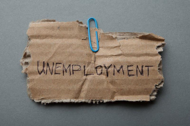 Wiadomość na starym drzejącym kartonie: «bezrobocie «na szarym tle obrazy stock
