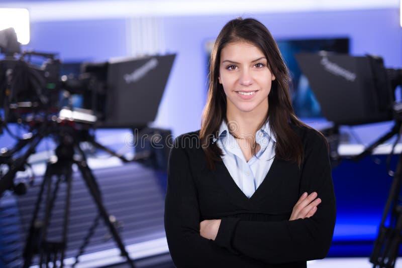 Wiadomość reportaż i writing Kobieta dziennikarz w telewizyjnej pracownianej pozyci z jej rękami krzyżować obraz royalty free