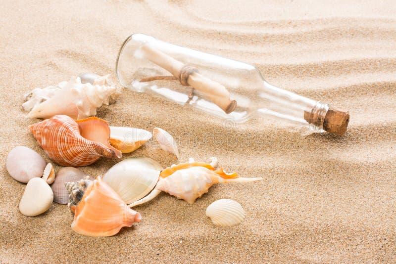 Wiadomość w butelce na plaży Lata tło z gorącym piaskiem obrazy royalty free