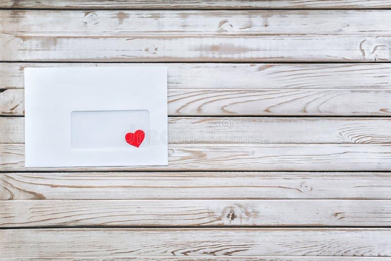 wiadomość wystrzelona blisko miłości, Czerwony serce w białej kopercie List o miłości zdjęcie stock