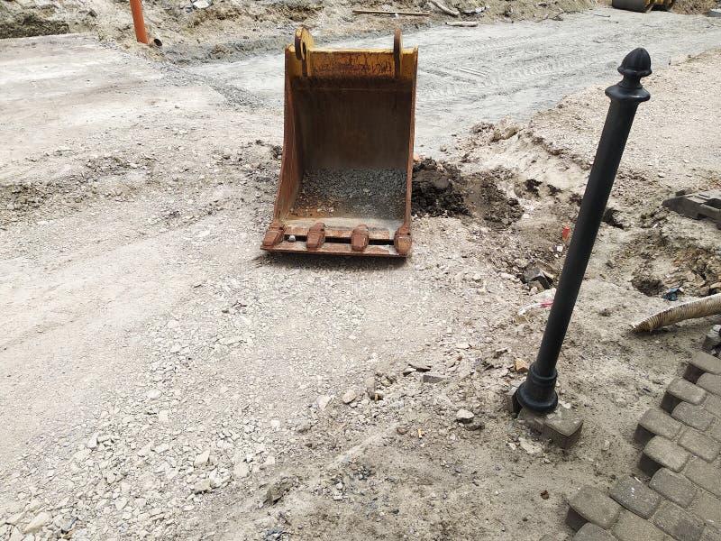 Wiadro od ekskawatoru jest na drodze bez asfaltu naprawa drogi, zastępstwo asfalt, poręcz, brukowe cegiełki i ogrodzenia, zdjęcie stock