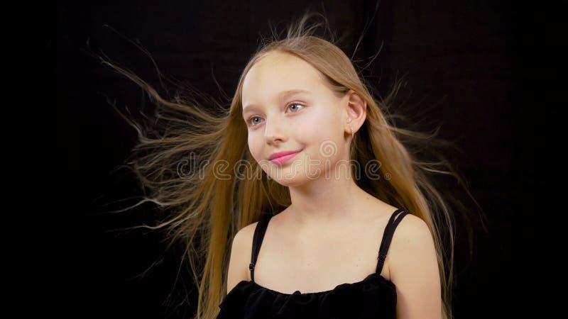 Wiatrowy dmuchanie na dziewczyny twarzy Zamyka w górę, śliczna urocza mała wzorcowa caucasian dziewczyna z trzepoczę włosiany pat zdjęcie royalty free