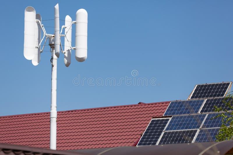 Wiatrowy generator i panel słoneczny na dachu dom, czysta energia odnawialna, w górę obrazy royalty free