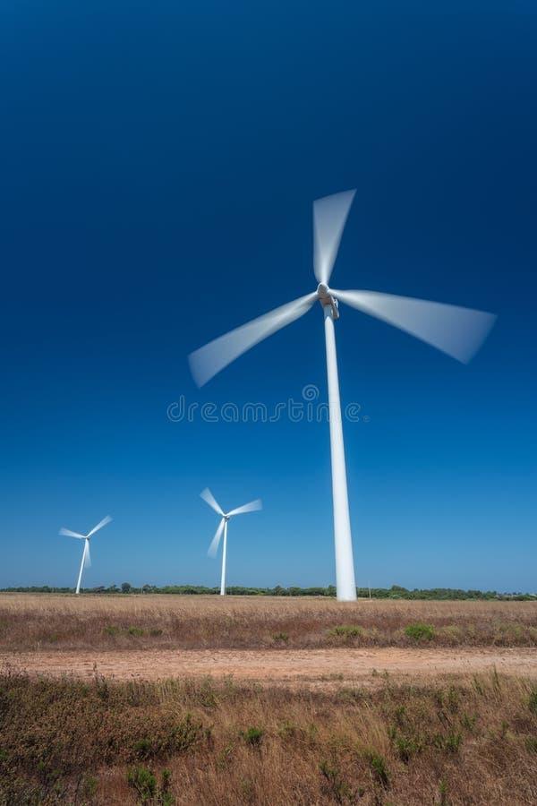 Wiatrowy Wytwarzać stacjonuje, w ruchu drogowym, na tle niebieskie niebo obraz stock