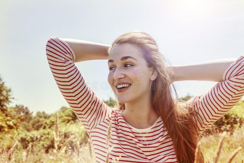 Wibrująca wspaniała młoda kobieta z wiatrem w długie włosy ono uśmiecha się fotografia stock