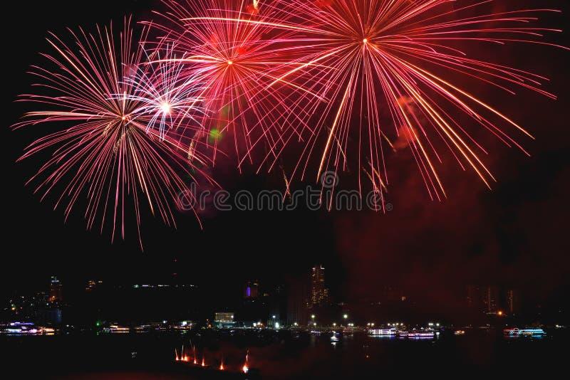 Wibrujący czerwoni fajerwerki bryzga w miasta nocnym niebie zdjęcia stock