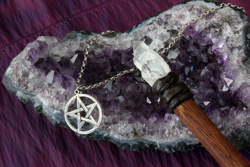 Wiccan Objects. Close up of wiccan objects - pentacle pendant, wood / crystal wand and amethyst geode royalty free stock images