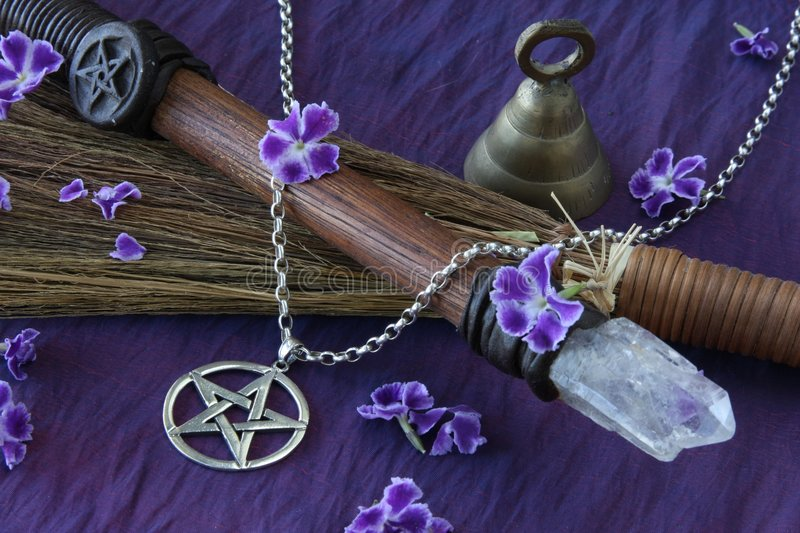 Wiccan Objects. Close up of wiccan objects - pentacle pendant, wood / crystal wand and straw besom royalty free stock photos