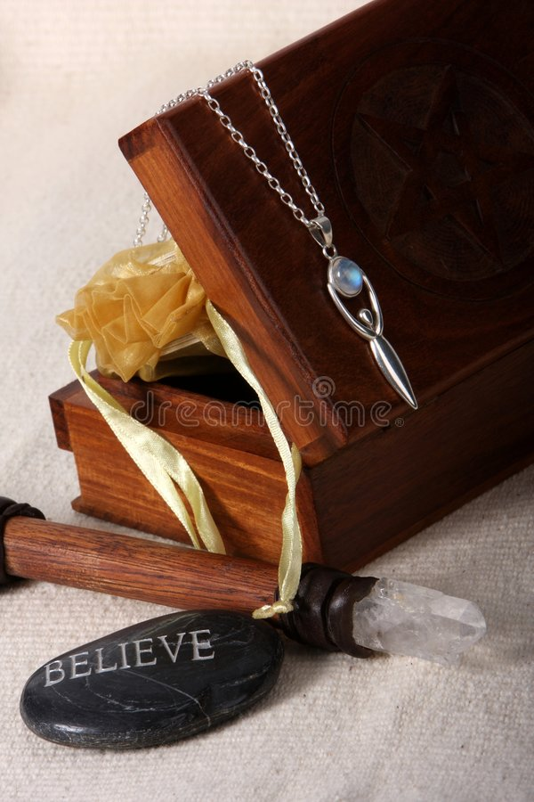 Wiccan Objects. Close up of wiccan objects - tarot cards, box, wand, goddess pendant, believe stone stock photography