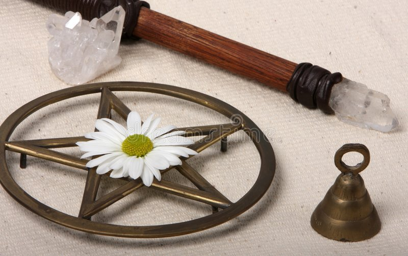 Wiccan Objects. Close up of wiccan objects - pentacle wand bell crystal and flower stock photos