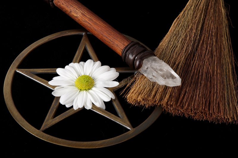 Wiccan Objects. Close up of wiccan objects - brass pentacle, wand, besom and flower on black background royalty free stock photos