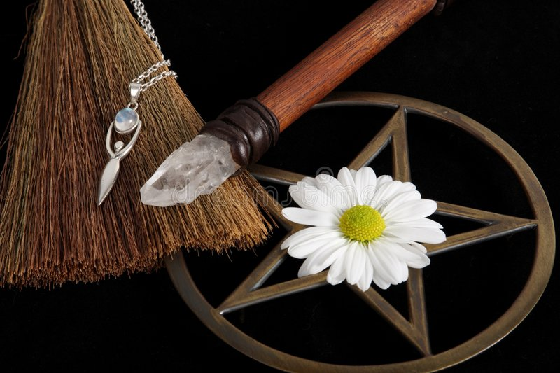 Wiccan Objects. Close up of wiccan objects - brass pentacle wand besom and flower with silver goddess pendant royalty free stock images