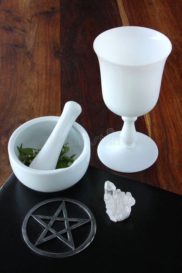 Wiccan Tools. Closeup of wicca spell tools and book of shadows with crystal cup mortar and pestle stock photo