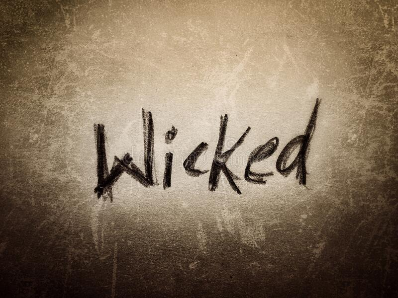 The wicked English word art written by hand pencil on the rough paper page wall texture design royalty free stock images