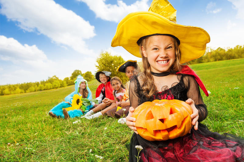 Wicked girl in witch dress with Halloween pumpkin royalty free stock image