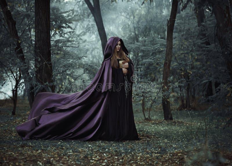 Wicked witch in a long dark cloak wandering in woods stock photo