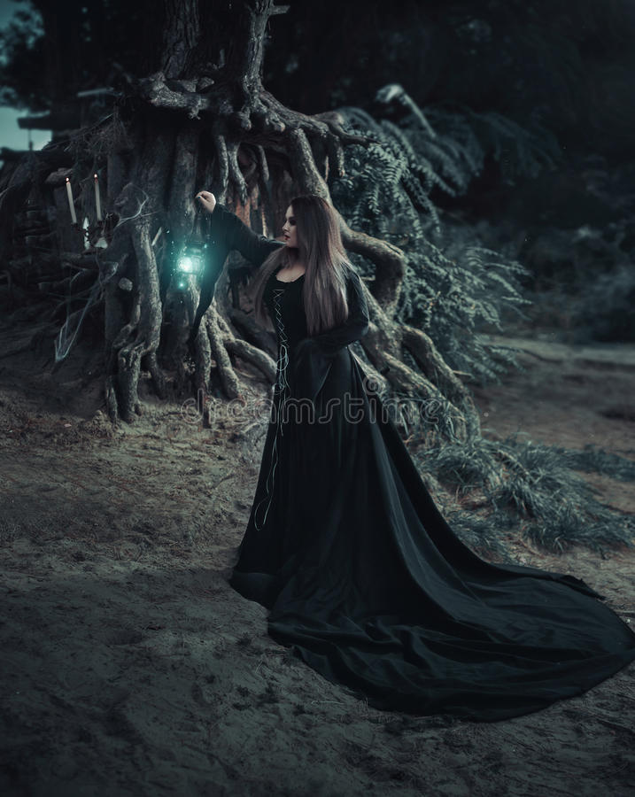 Wicked witch in a long vintage dress, evokes the spirit stock photo