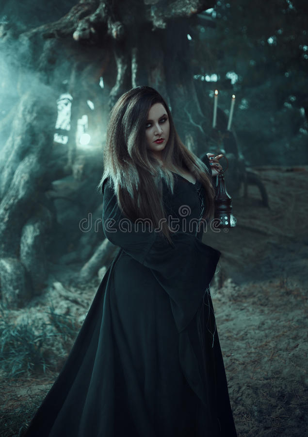 Wicked witch in a long vintage dress, holding a magic lamp . stock images