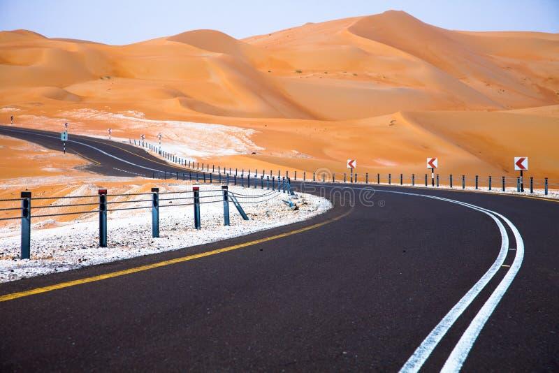 Wickelnde schwarze Asphaltstraße durch die Sanddünen von Liwa-Oase, Vereinigte Arabische Emirate stockbild