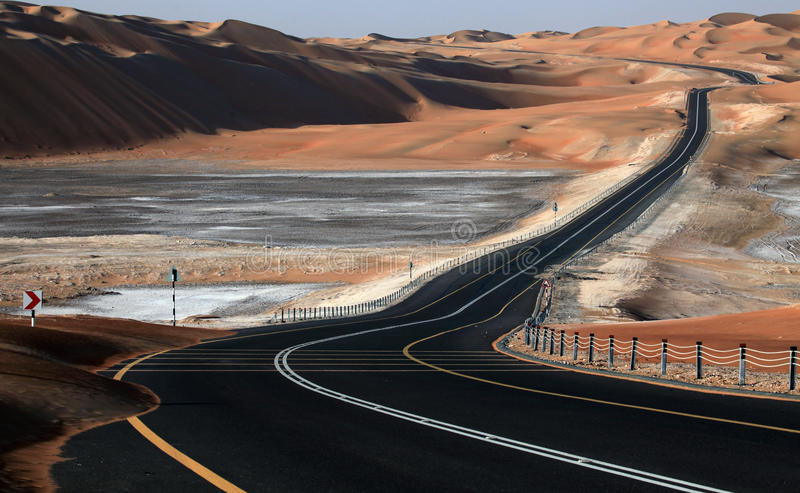 Wickelnde schwarze Asphaltstraße durch die Sanddünen von Liwa-Oase, Vereinigte Arabische Emirate stockbilder