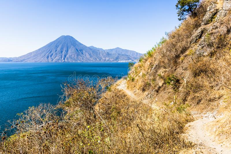 Wickelnder Schmutz clifftop Fußweg, Seeblick u. Vulkan, See Atitlan, Guatemala lizenzfreie stockfotos