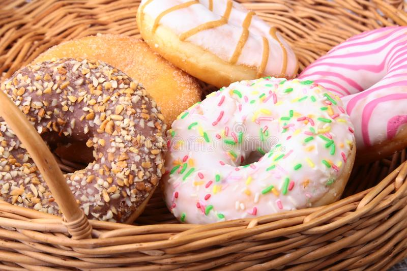 Wicker basket with assorted delicious homemade doughnuts in the glaze, colorful sprinkles and nuts . stock images