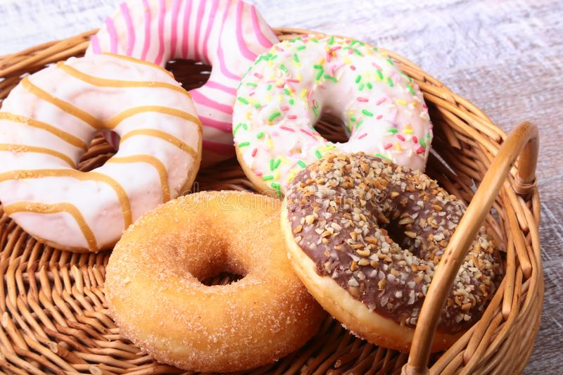 Wicker basket with assorted delicious homemade doughnuts in the glaze, colorful sprinkles and nuts . royalty free stock photos
