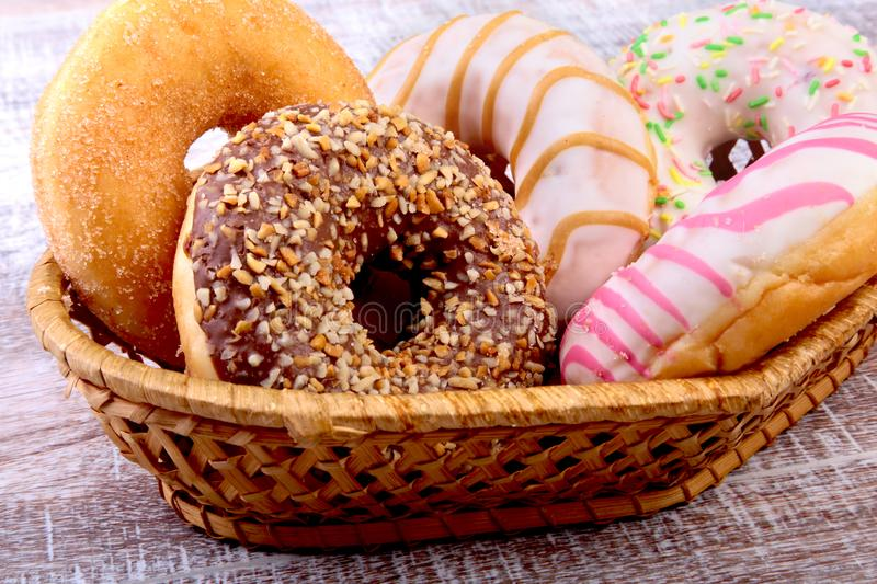 Wicker basket with assorted delicious homemade doughnuts in the glaze, colorful sprinkles and nuts. Cupcakes. Top View stock image