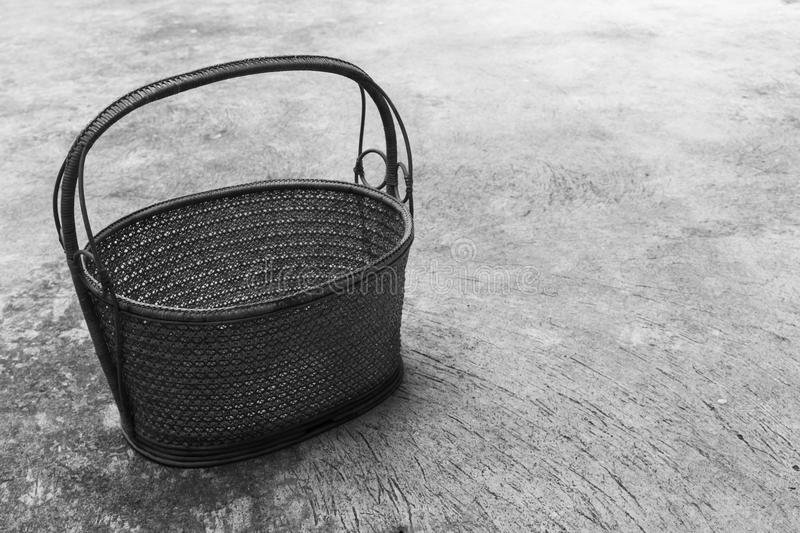 Wicker basket. On a cement ground as black and white background stock photography