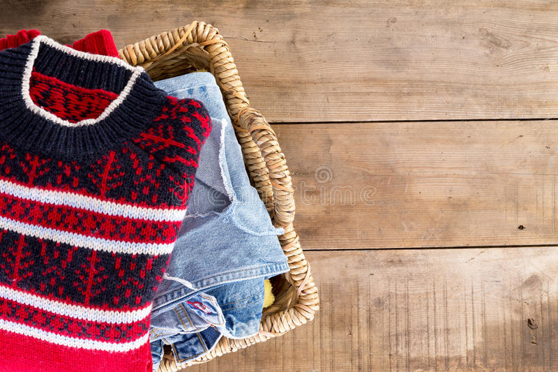 Wicker basket with clean fresh winter clothes. Wicker laundry basket filled with clean fresh washed winter clothes viewed from overhead standing at an angle on stock image