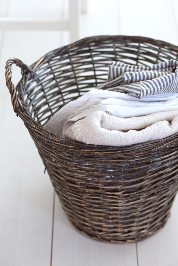 Wicker basket. Wicker clothes basket with cotton linen in it stock photo