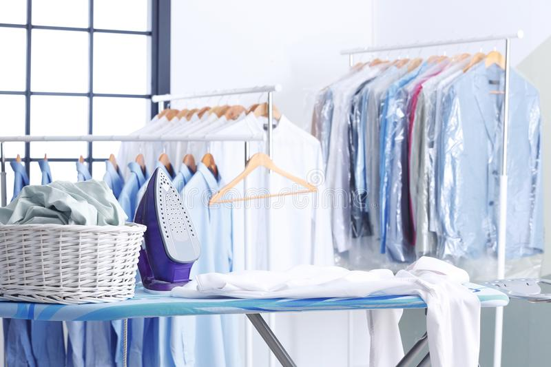 Wicker basket with clothes on ironing board. At dry-cleaner`s royalty free stock photography