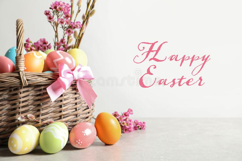 Wicker basket with colorful painted eggs on table and text Happy Easter stock photos