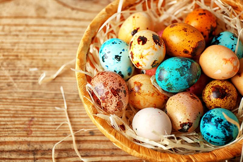 Wicker basket with colourful Easter eggs. On wooden table royalty free stock images