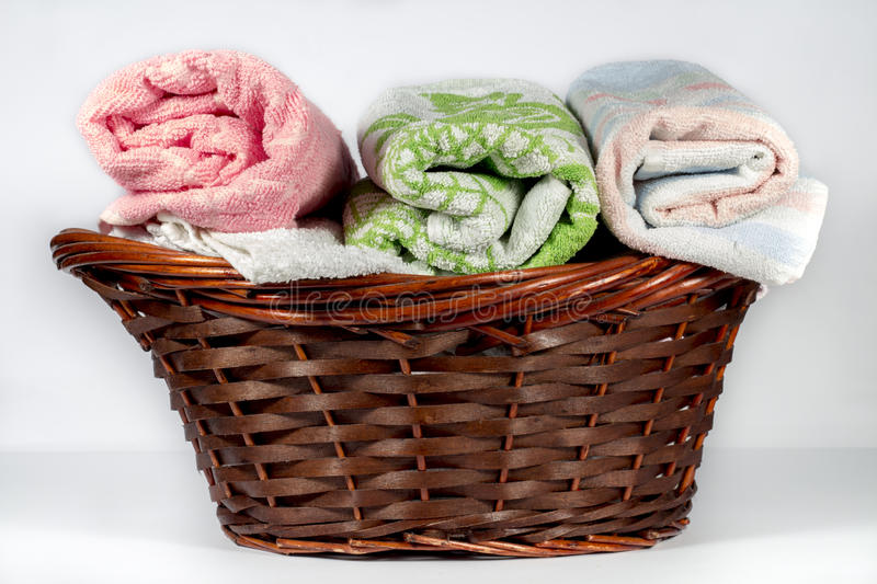 Wicker basket containing hand towels of different colors and patterns. Wicker basket for bathroom containing several hand towels of different colors and patterns stock image