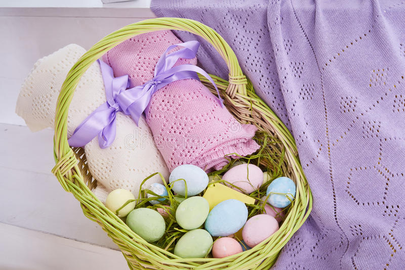 Wicker basket Easter set with colored eggs hay crocheted blankets covered with silk satin ribbon easter holy celebration, happy stock photography