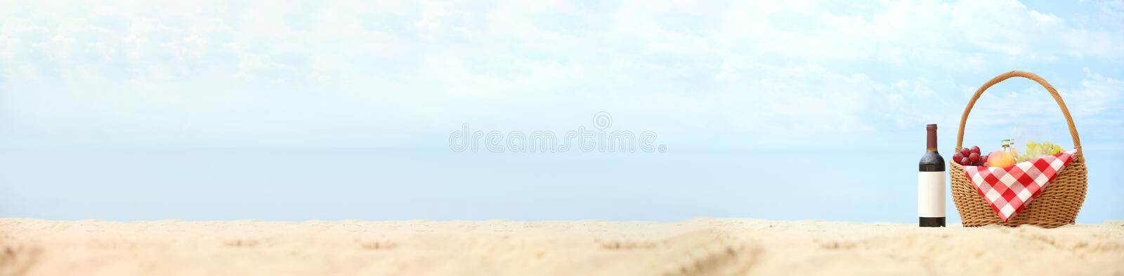 Wicker basket with food and wine on sand near sea. Beach picnic. Wicker basket with food and wine on sand near sea, space for text. Beach picnic royalty free stock images