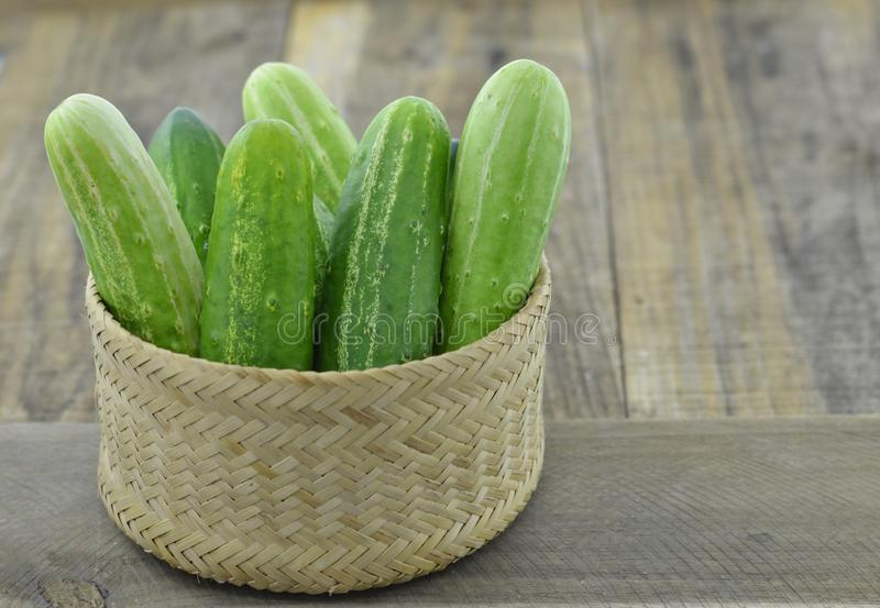 Wicker basket with fresh cucumber on wooden background royalty free stock photos